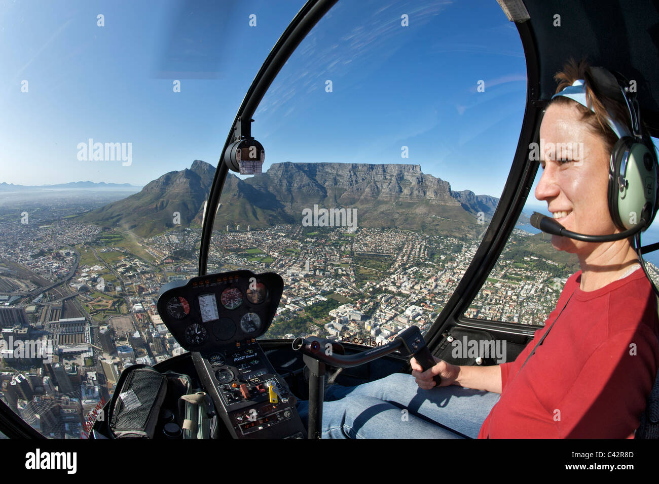 Young woman at the controls of a Robinson 22 helicopter flying over the city of Cape Town, South Africa. - Stock Image