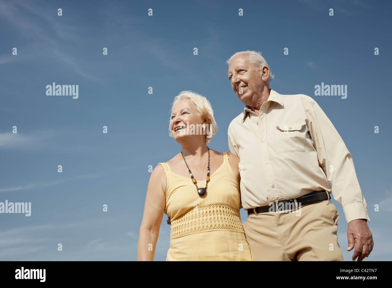 senior caucasian couple walking on sunny day and hugging. Horizontal shape, low angle view, copy space - Stock Image