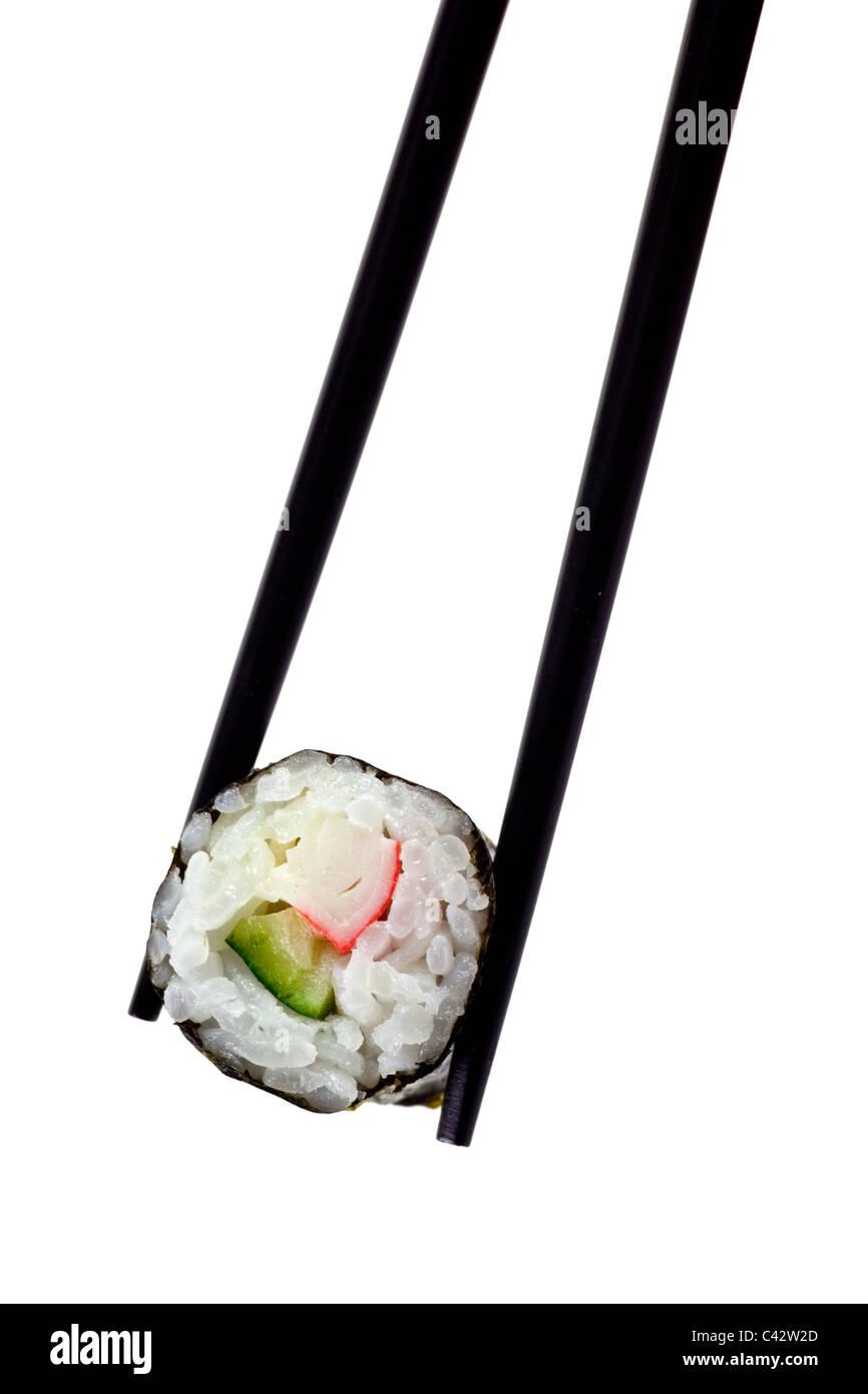 Chopsticks holding maki sushi isolated on white background - Stock Image