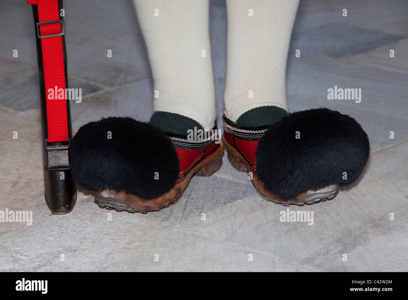 Red tsarouhi leather clogs with a black pompon of the Evzones at the Tomb of the Unknown Soldier  in Athens, Greece - Stock Image