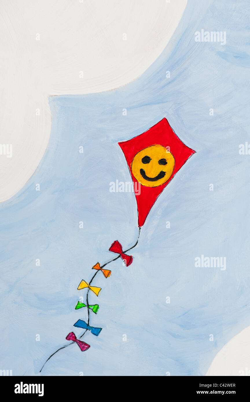 Childs painting of a happy smiling face on a kite in the sky Stock Photo