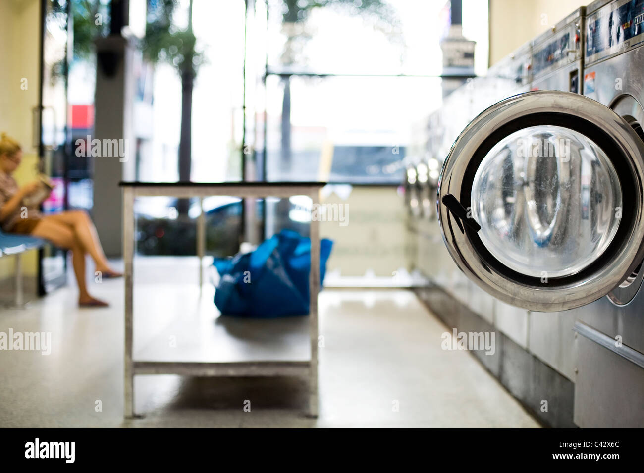 Girl waiting in laundromat - Stock Image