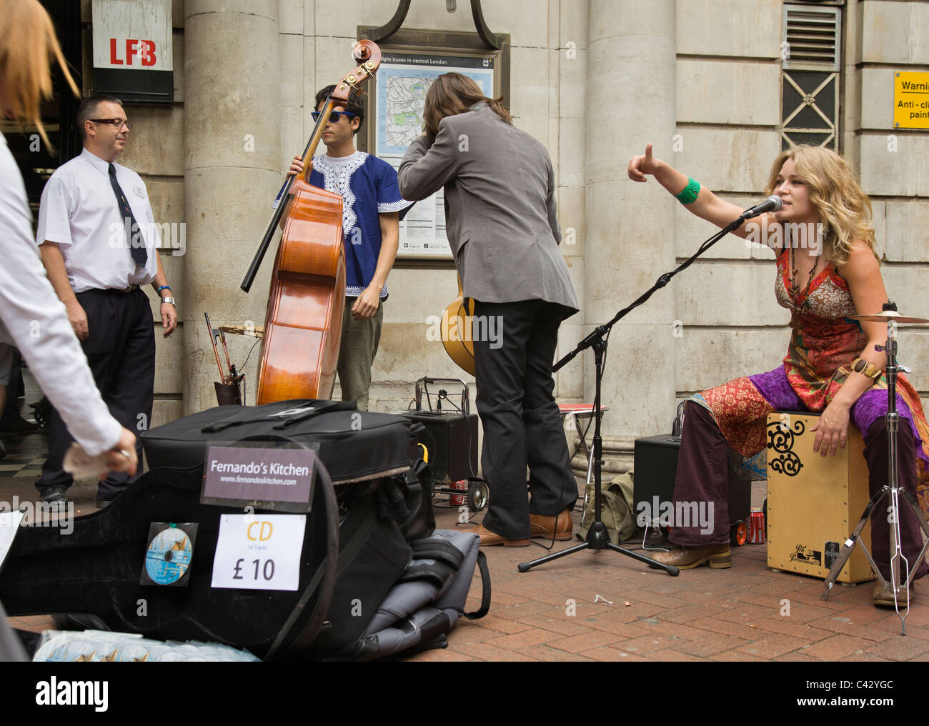 Musicians  pack up their kit as a TFL representative asks them to move away from the entrance to Embankment Tube. - Stock Image
