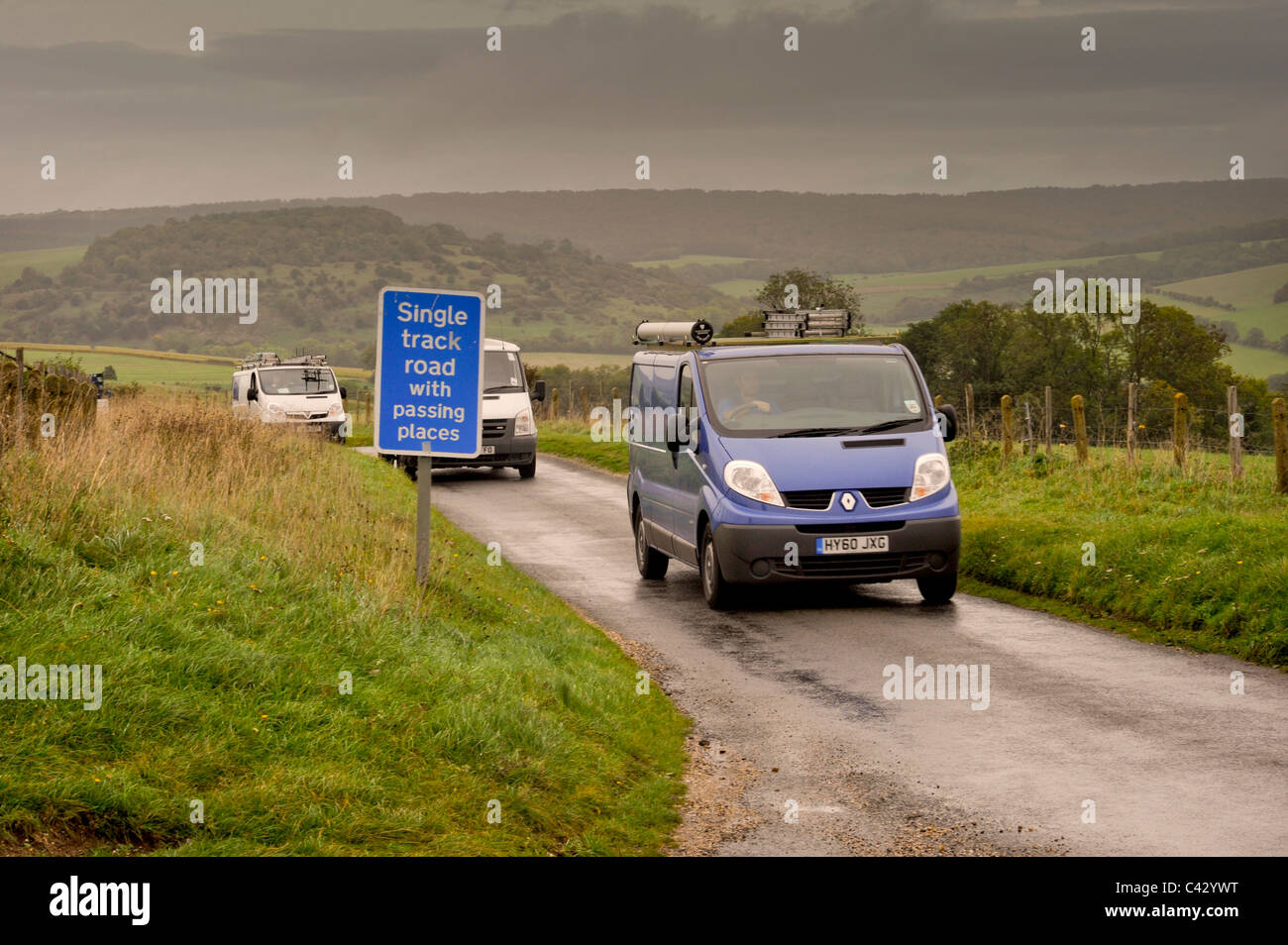 Several vans squeeze through a single track road high on the downs above Chichester in West Sussex. Stock Photo