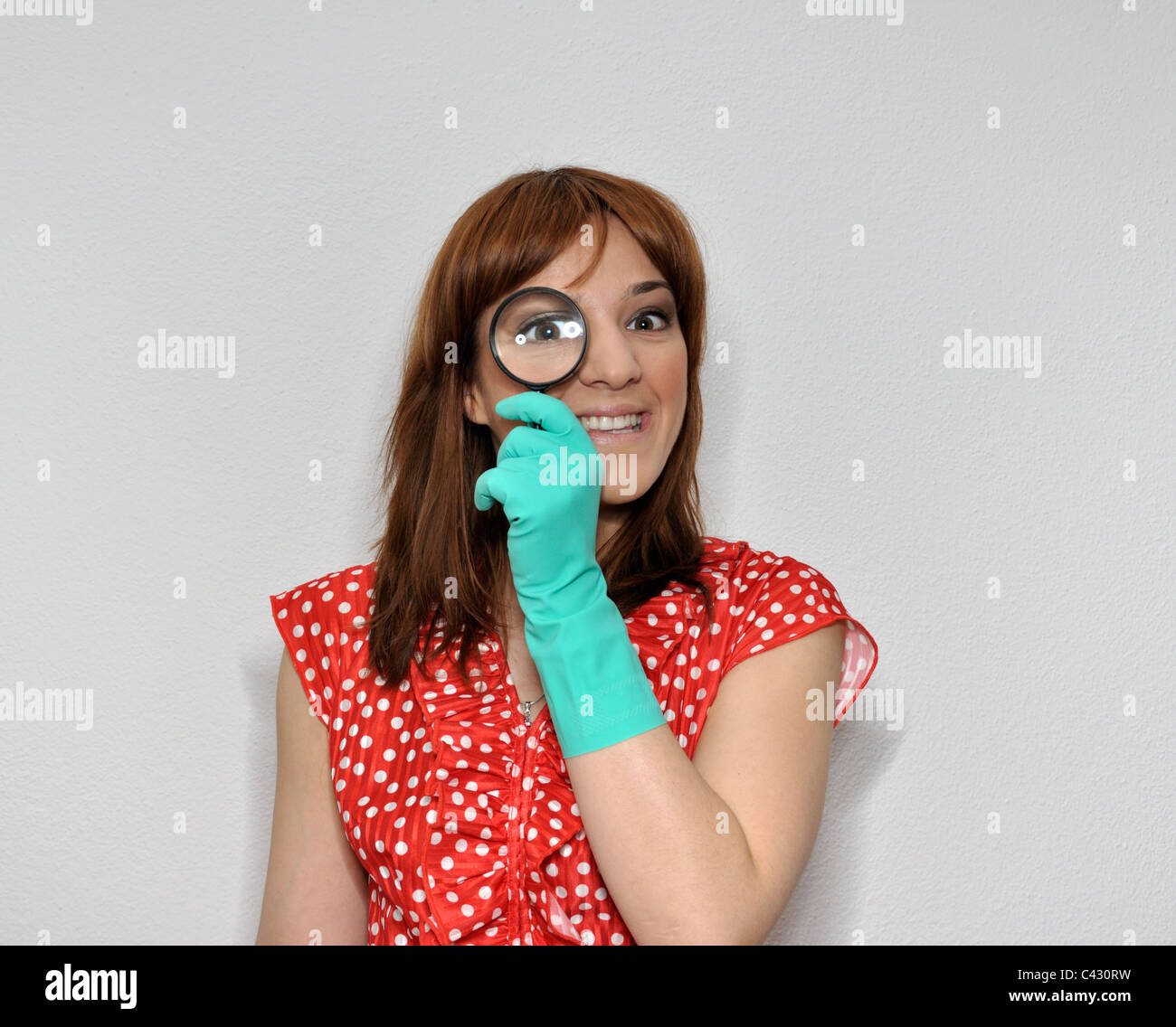 Young woman wearing rubber gloves looking trough magnifying glass - Stock Image