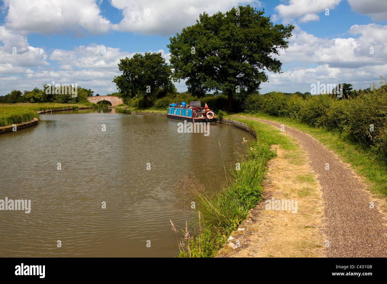 A view along the towpath on a bright sunny day with a canal boat and a bridge in the distance. - Stock Image