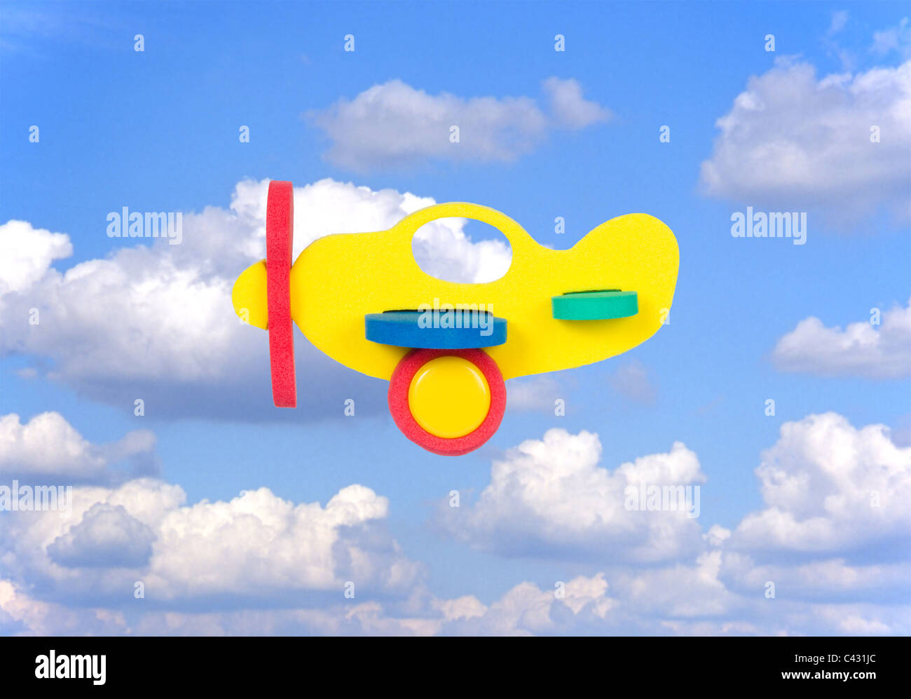 toy aeroplane cut-out against blue sky background with clouds - Stock Image