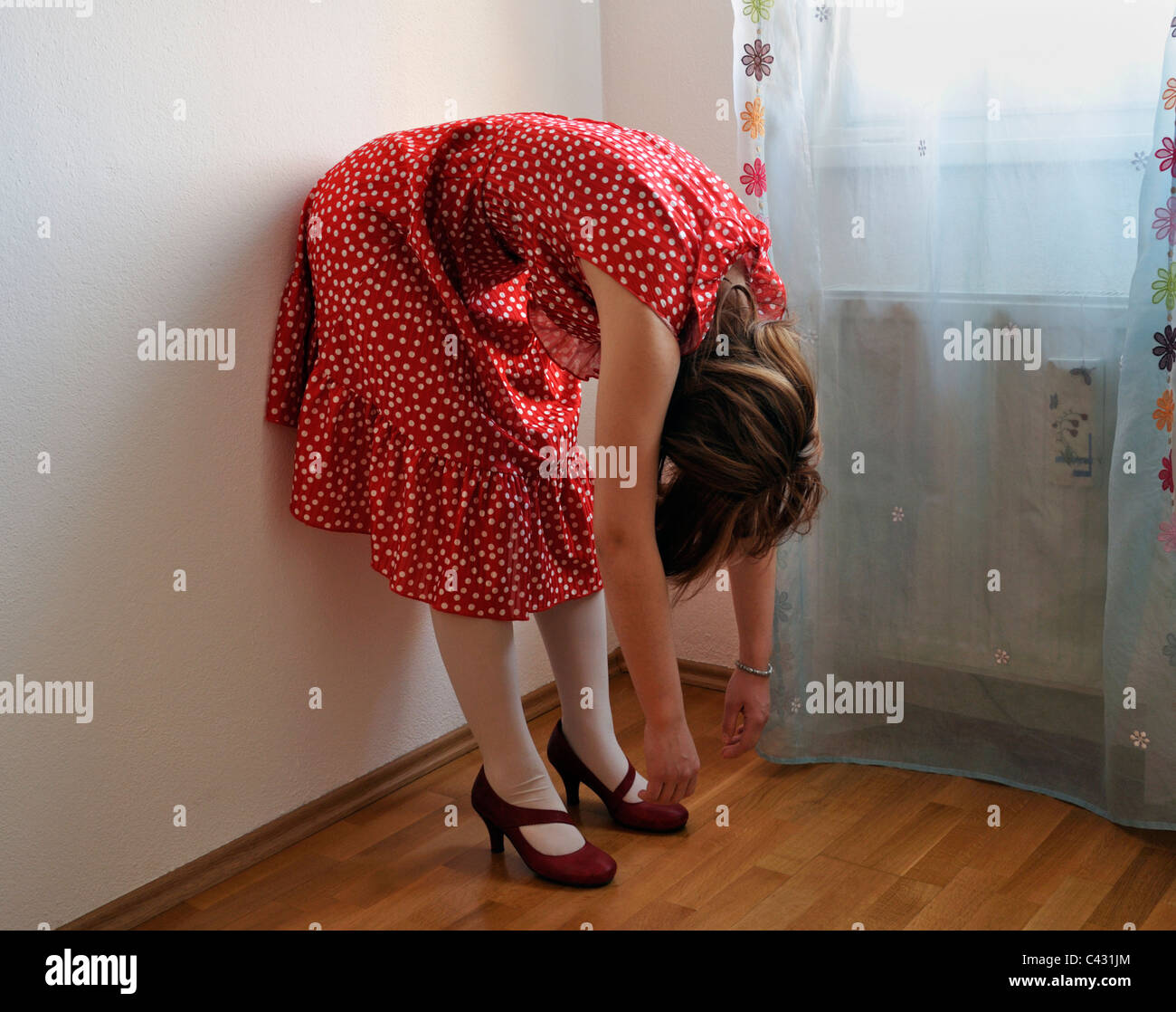 Young woman wearing polka dot dress bending over - Stock Image