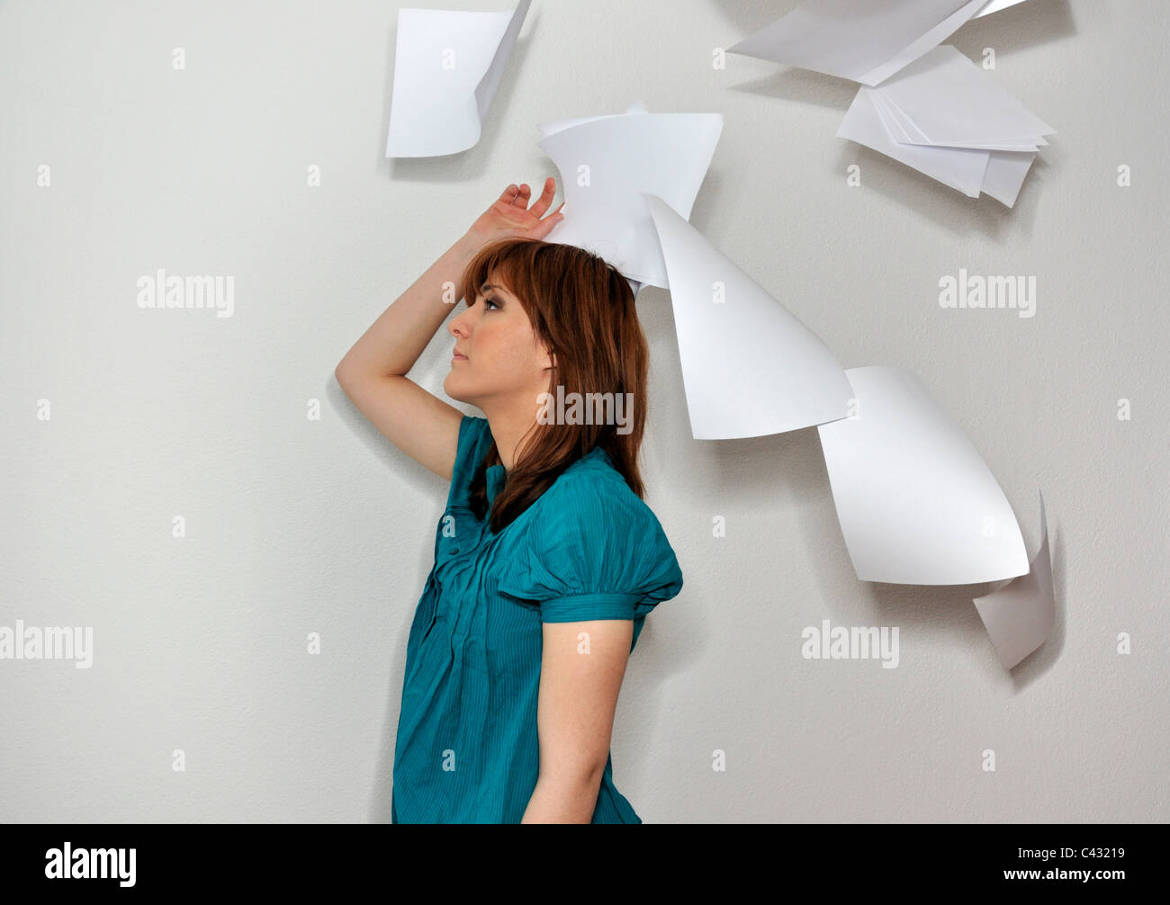 Young woman throwing paperwork in air - Stock Image