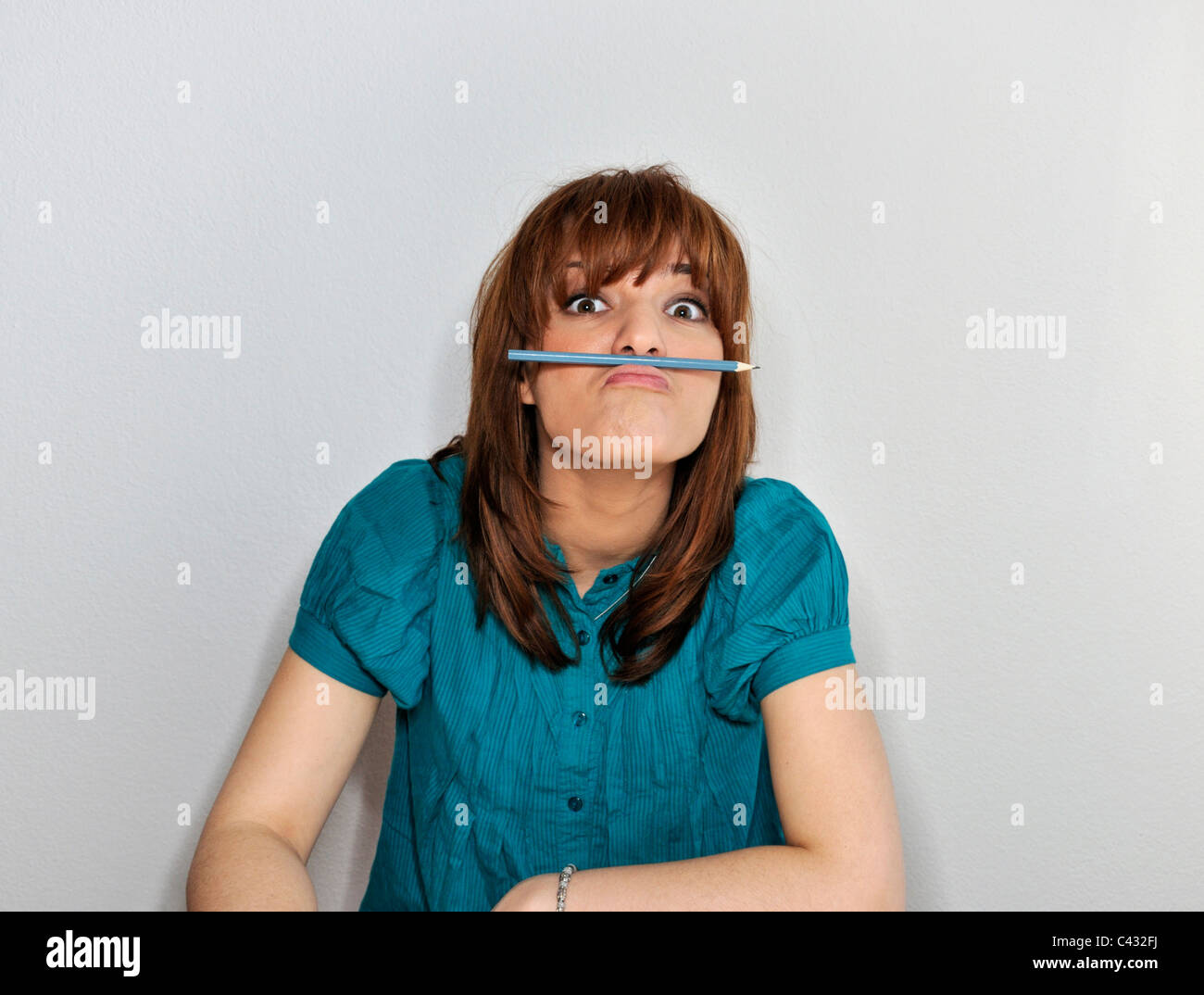 Young woman with pencil between lip and nose - Stock Image