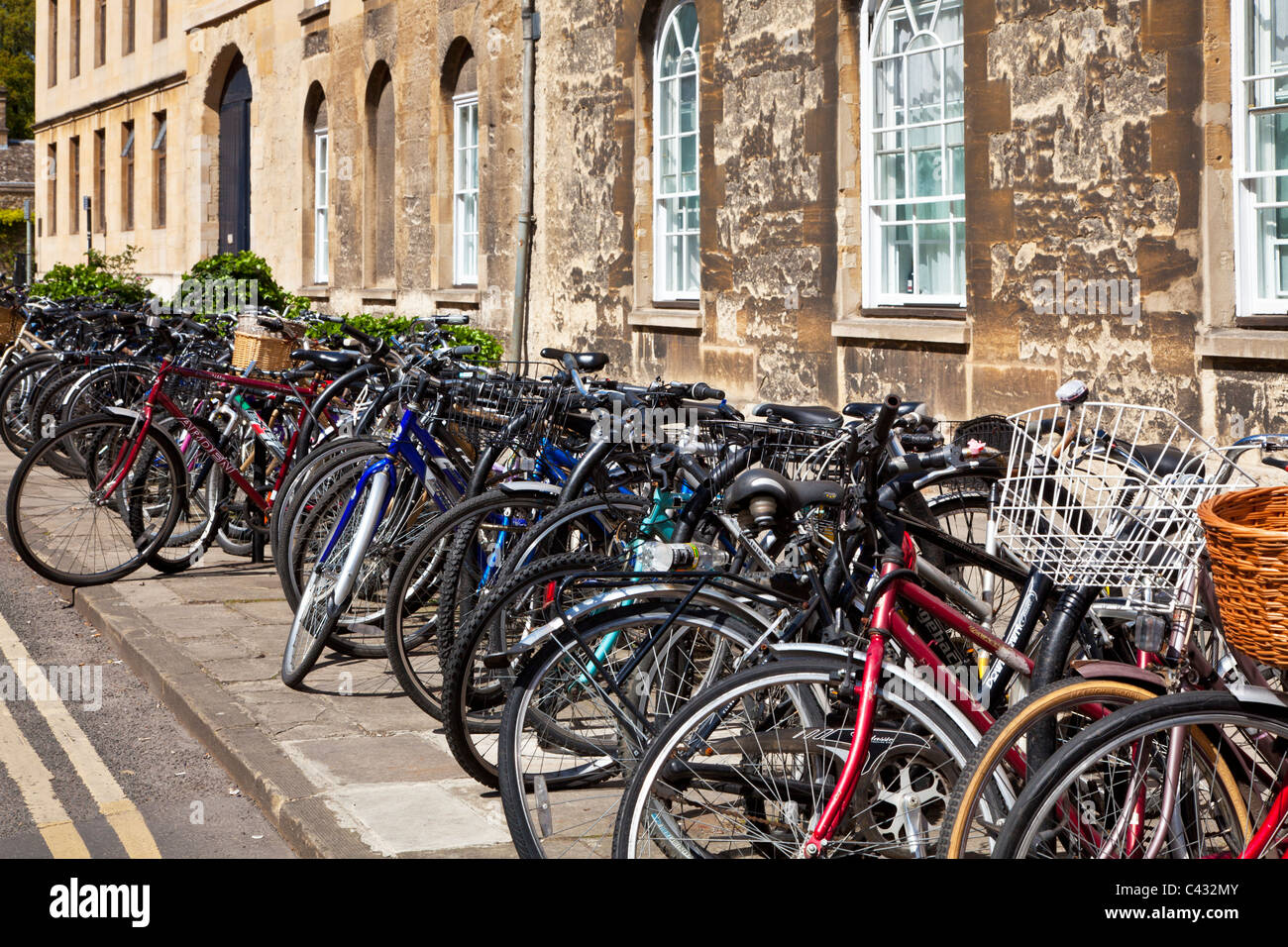 Bicycles against a wall in Parks Road, Oxford, Oxfordshire, England, UK, Great Britain - Stock Image