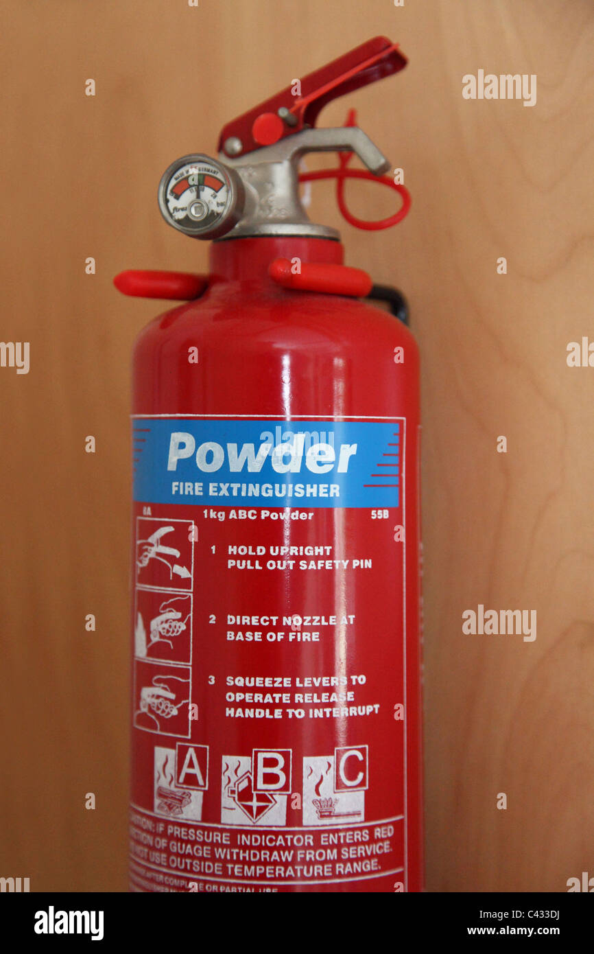 A wall mounted fire extinguisher. - Stock Image