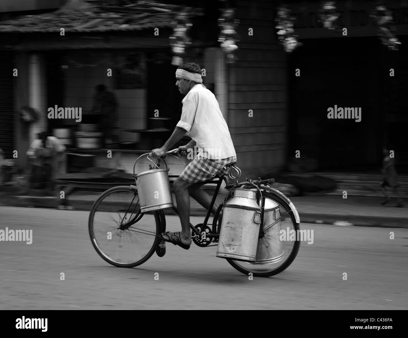 Panning portrait in black and white of a milk wallah on bicycle from Kolkata, West Bengal, India - Stock Image