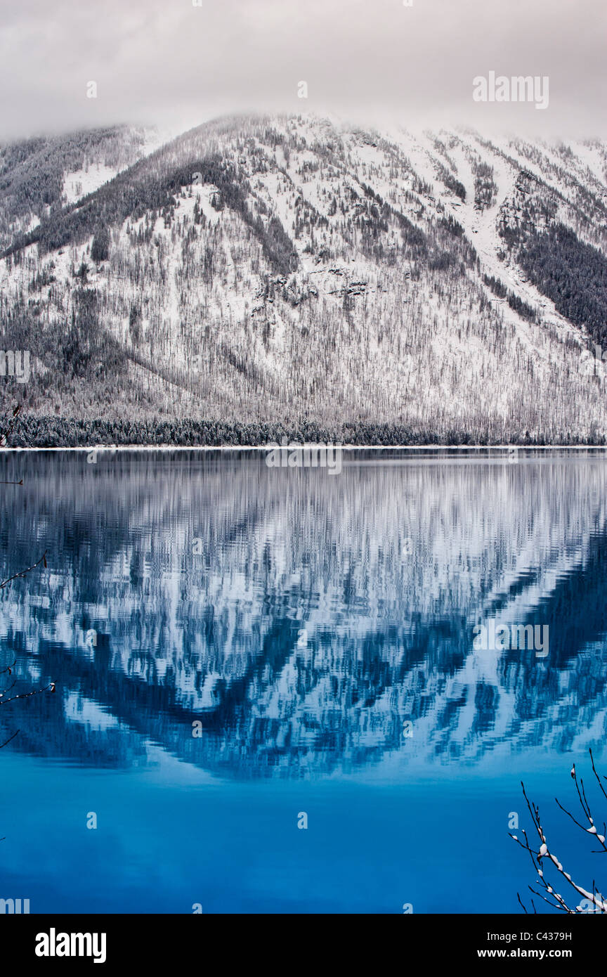 Snow-covered mountainsides reflect in Lake McDonald in Glacier National Park. - Stock Image