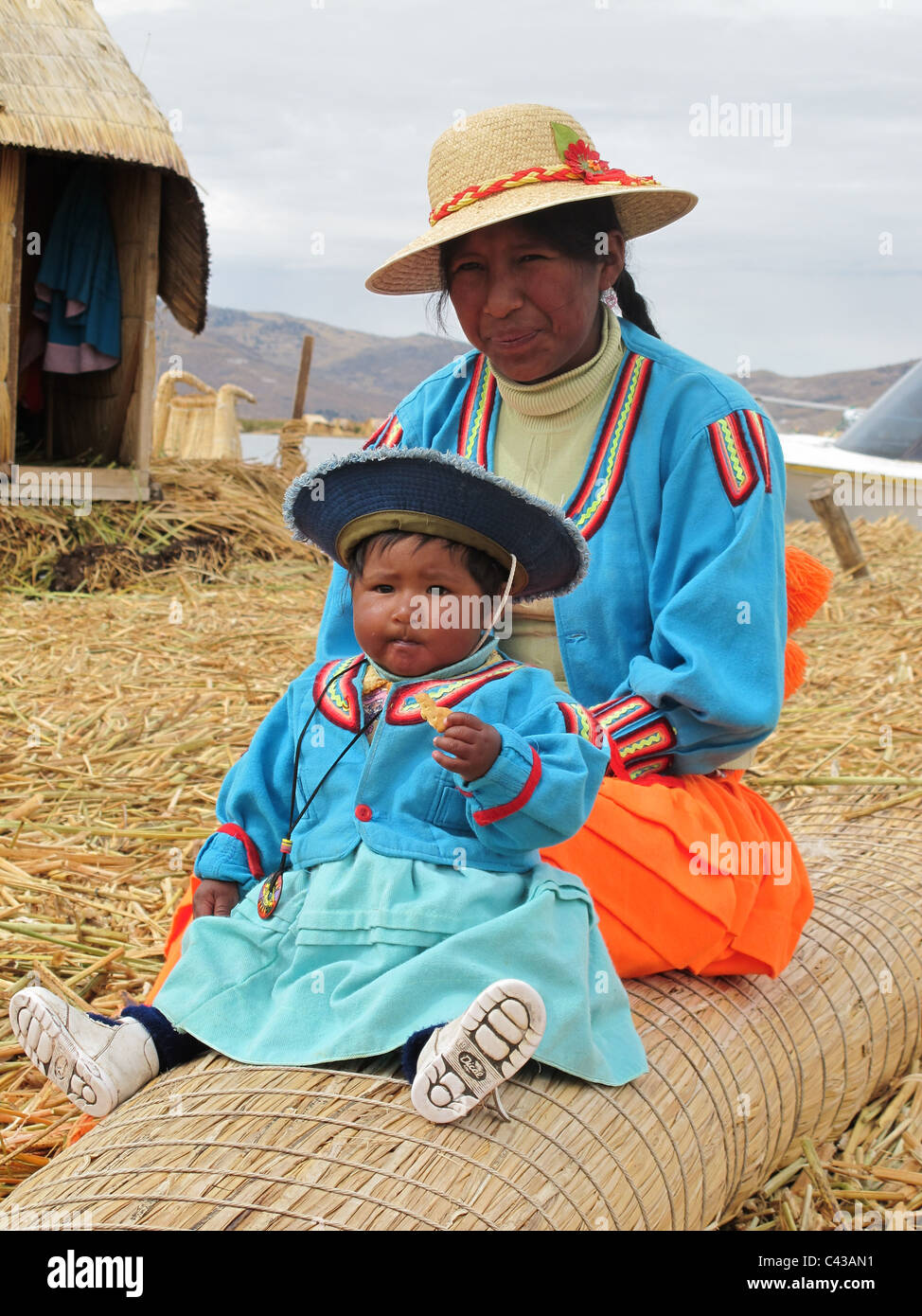 Uro mother and child traditionally dressed sitting on a reed bench in front of their reed house on the floating - Stock Image