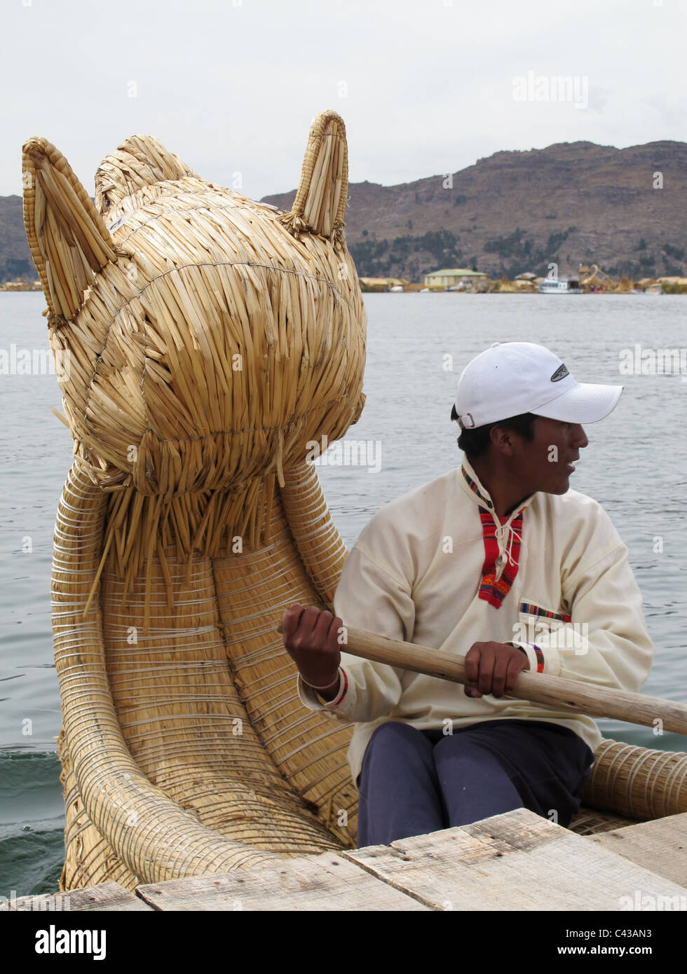 Uro man rowing his reed boat with dragon head for guests, lake titicaca, Peru - Stock Image