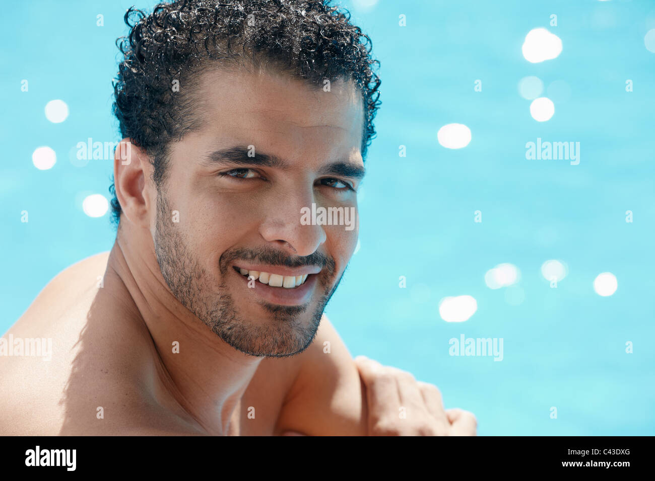 Handsome happy young hispanic man smiling and relaxing near hotel pool. Horizontal shape, head and shoulders, copy - Stock Image