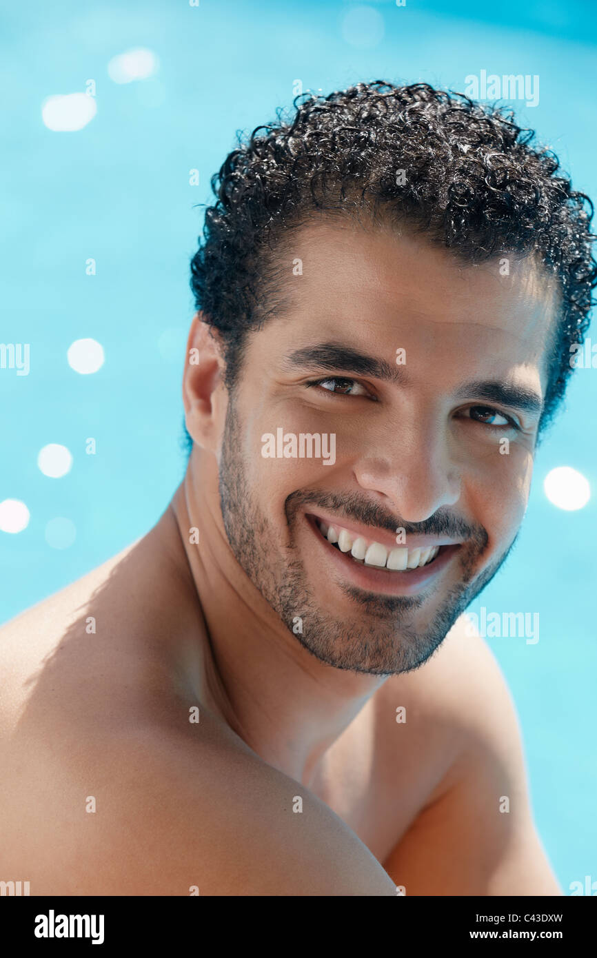 Handsome happy young hispanic man smiling and relaxing near hotel pool. Vertical shape, head and shoulders - Stock Image