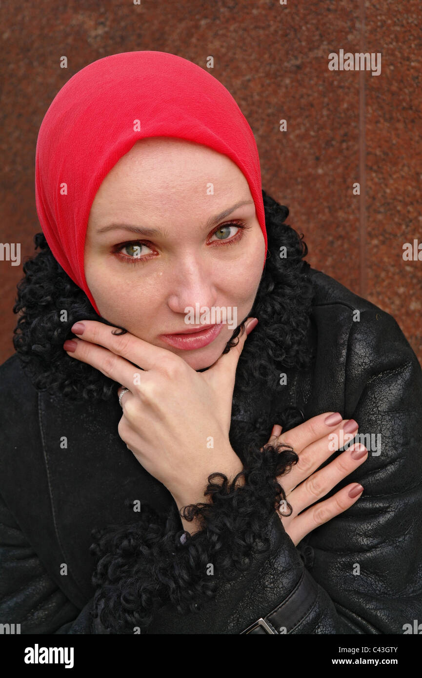 The girl in a red scarf and a black coat longs and cries, Moscow, Russia - Stock Image