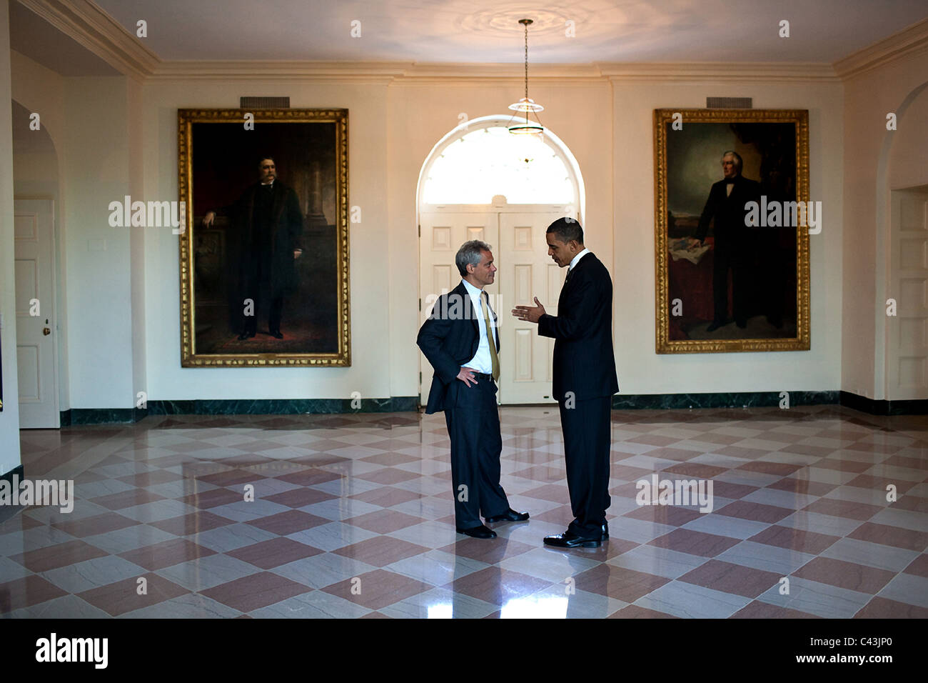 President Barack Obama talks with Chief of Staff Rahm Emanuel in the East Garden Room of the White House - Stock Image