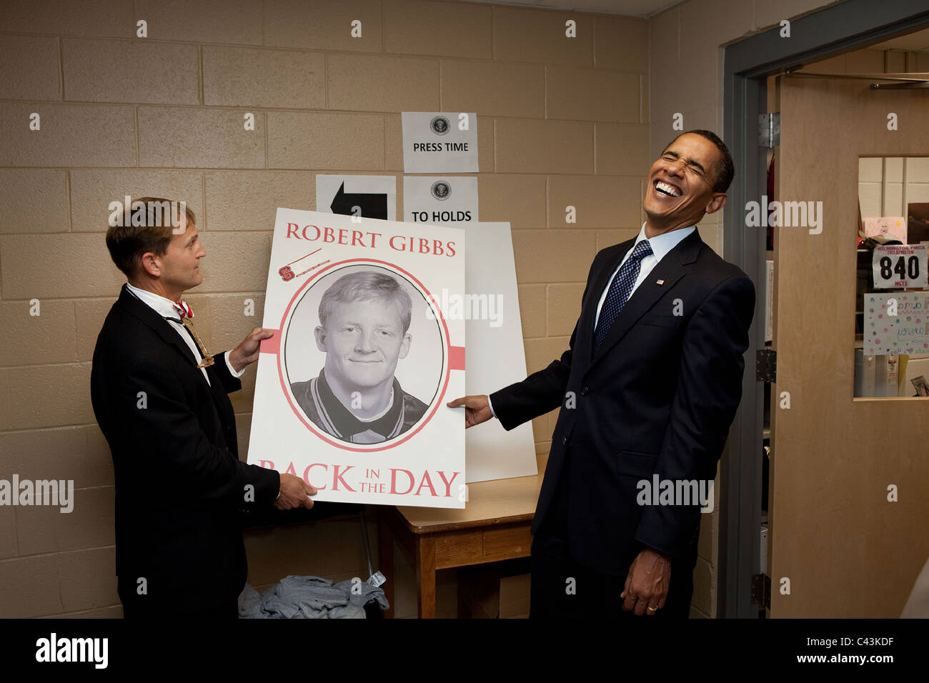 President Barack Obama laughs at a picture of a younger Press Secretary Robert Gibbs following a town hall meeting - Stock Image
