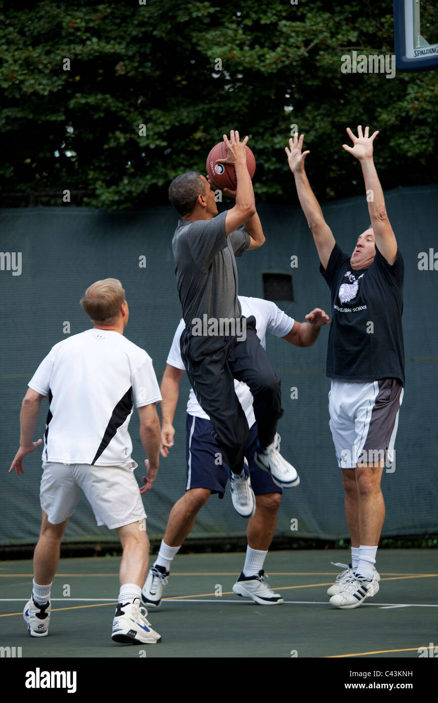 President Barack Obama takes a shot during a basketball game with Cabinet Secretaries and Members of Congress - Stock Image