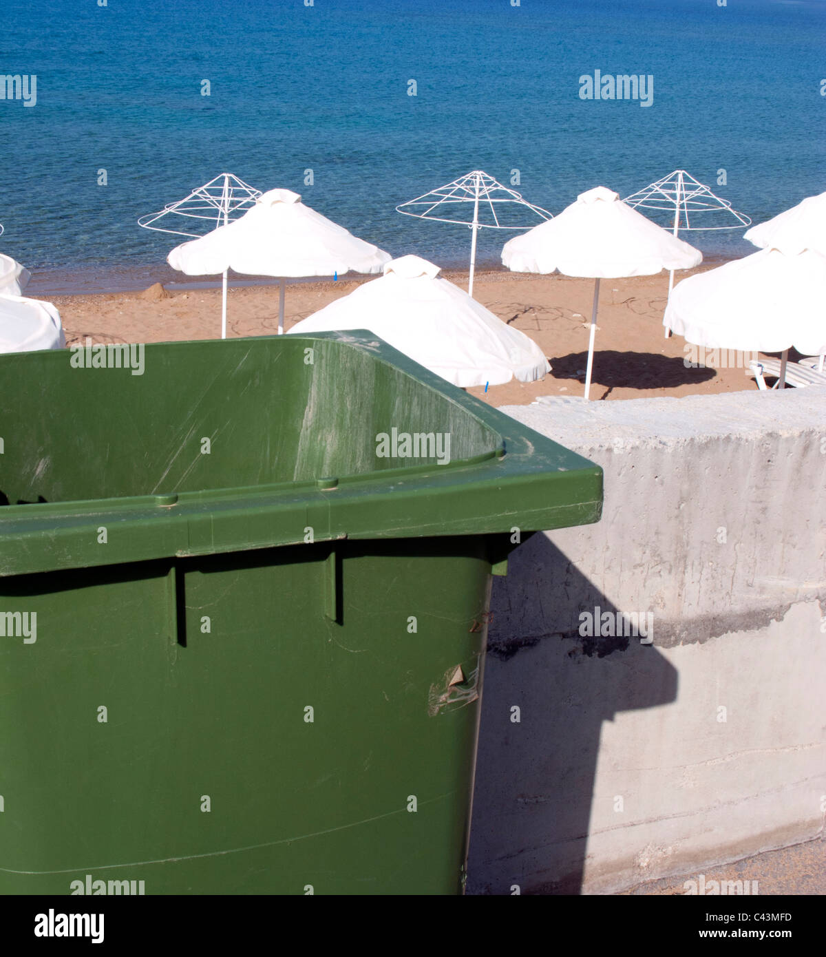 GREEN RUBBISH BIN BESIDE AN EMPTY BEACH IN GREECE Stock Photo
