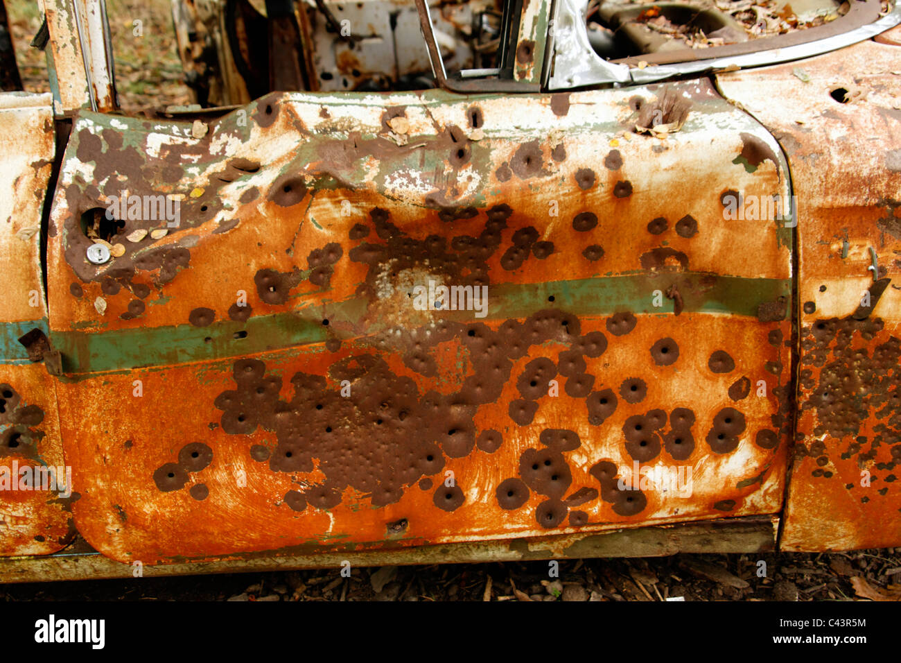 old car, door, riddled with bullet holes, rusted, rusty, target practice, waste, garbage - Stock Image