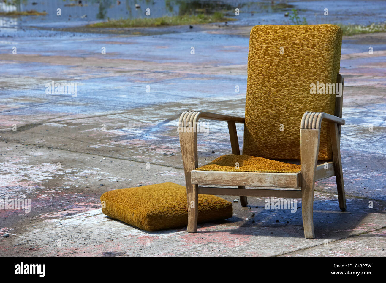 old discarded 70s yellow armchair furniture thrown away - Stock Image