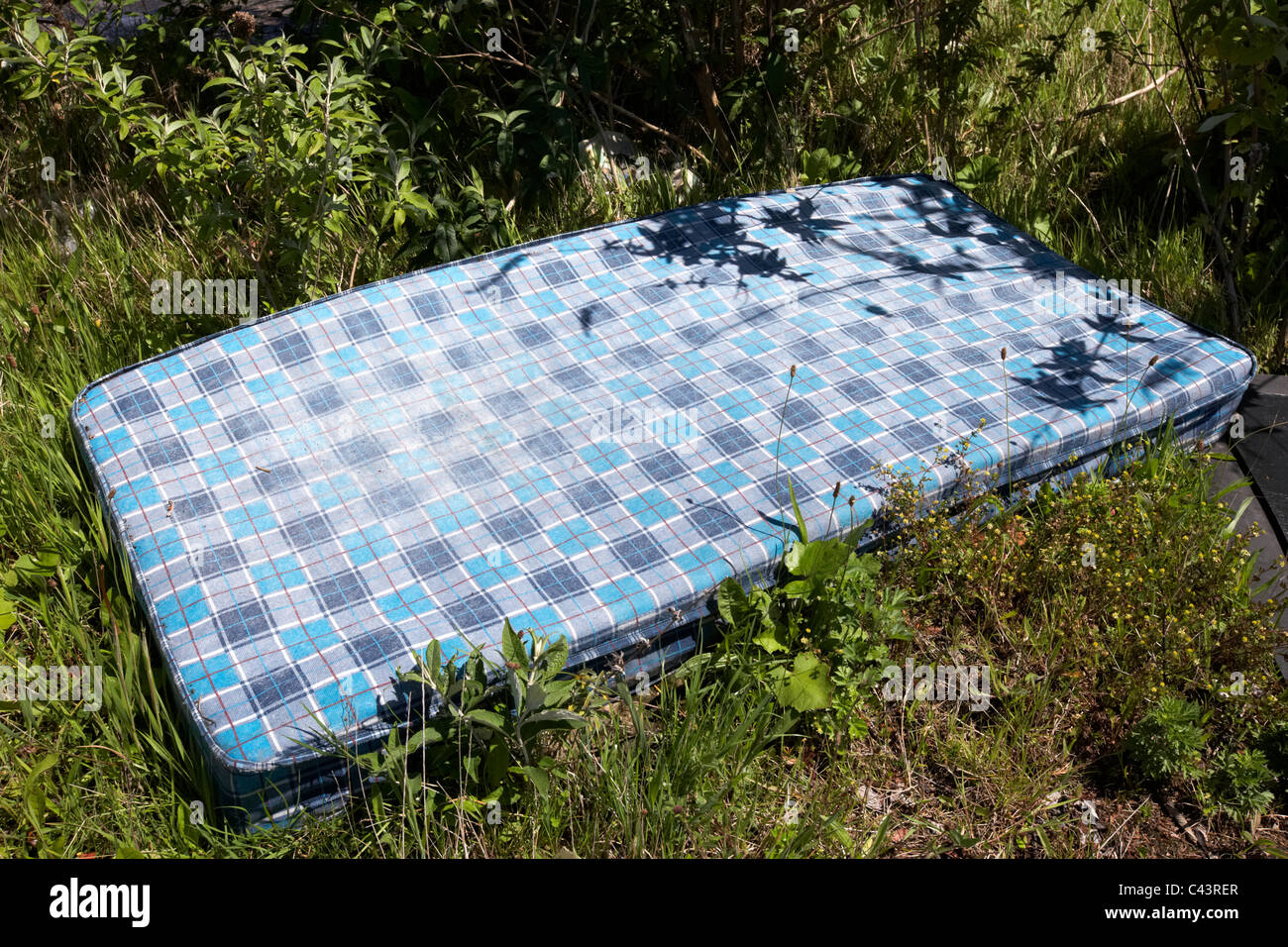 old mattress thrown away discarded by the roadside dumped - Stock Image