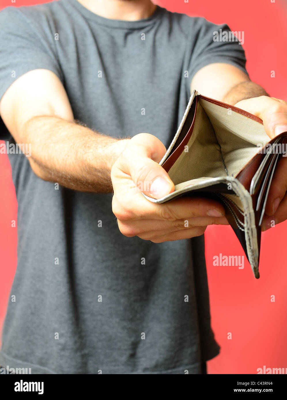 Man displaying empty wallet - Stock Image