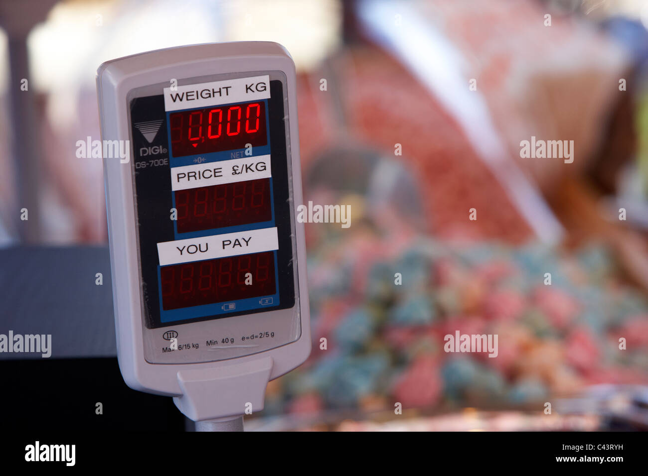 digital weighing scales on a sweet confectionery stall in a market - Stock Image