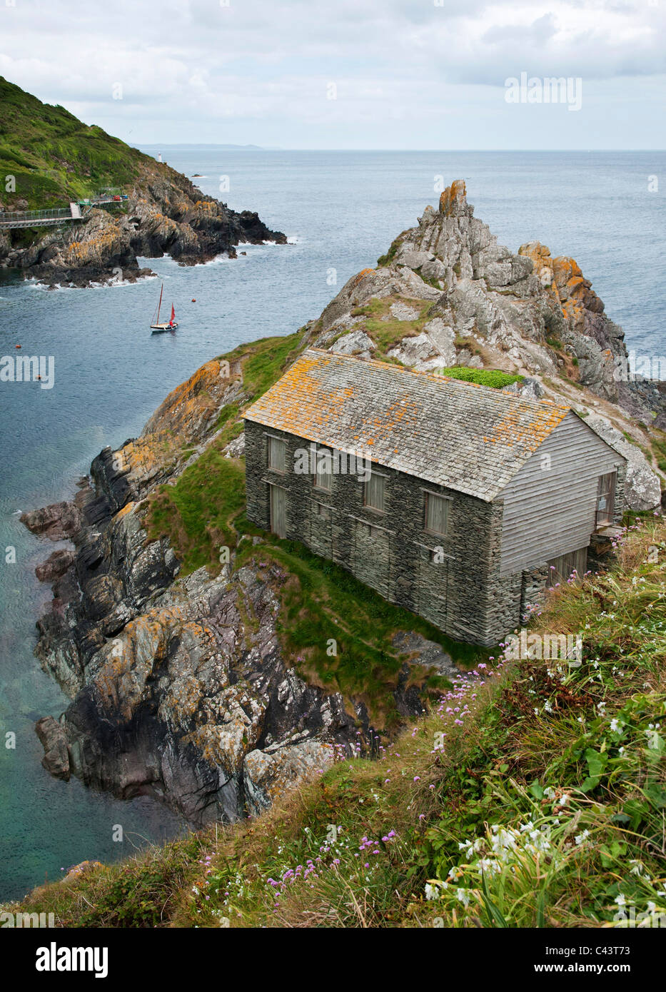 Old net loft at entrance to harbour of fishing village of Polperro, Cornwall UK - Stock Image