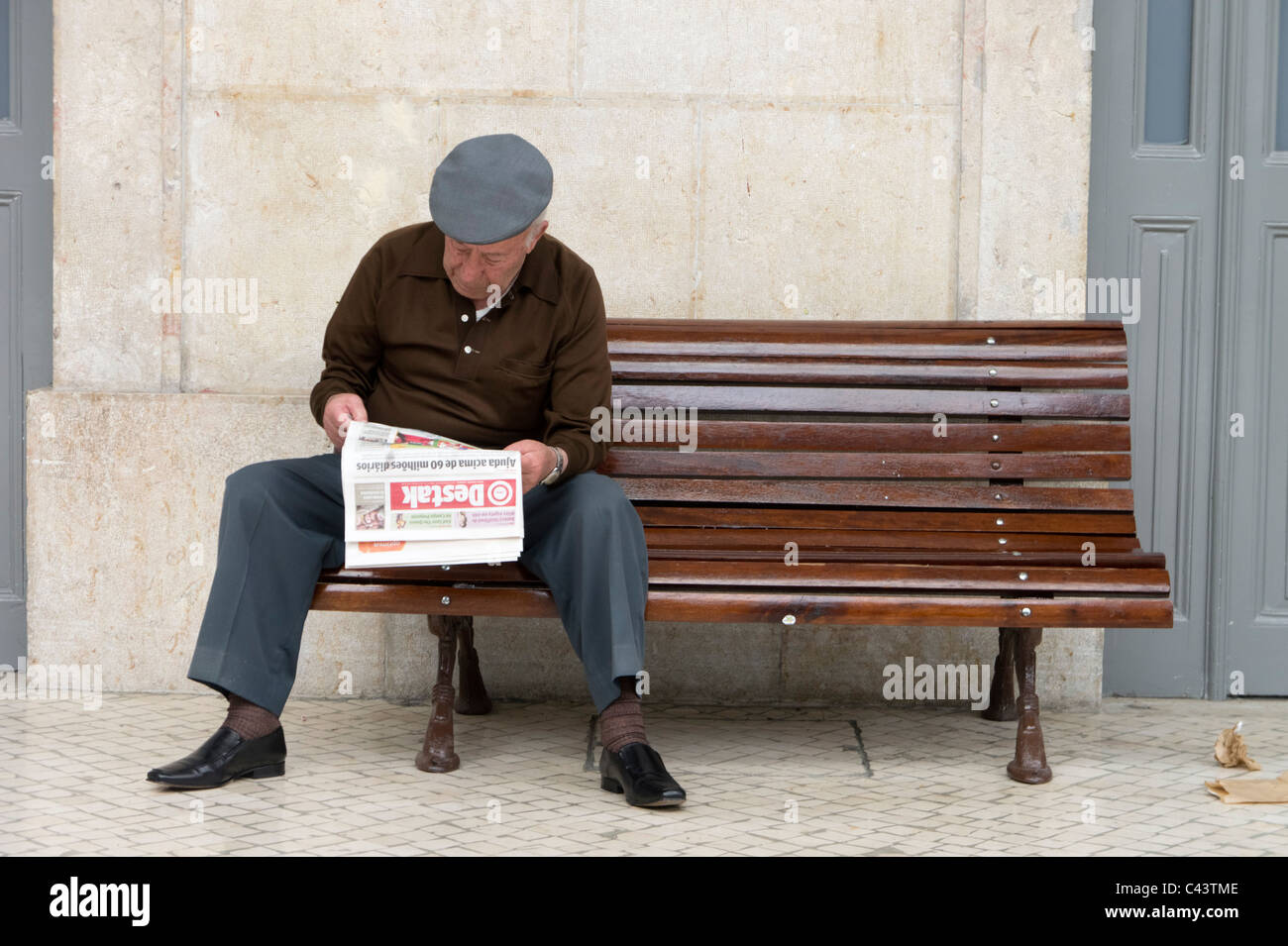 old man reading newspaper on a public bench stock photo: 36964606