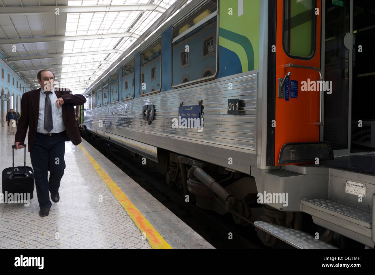 Passenger with suitcase next to an intercity train in Santa Apolónia railway station in Lisbon, Portugal, Europe - Stock Image