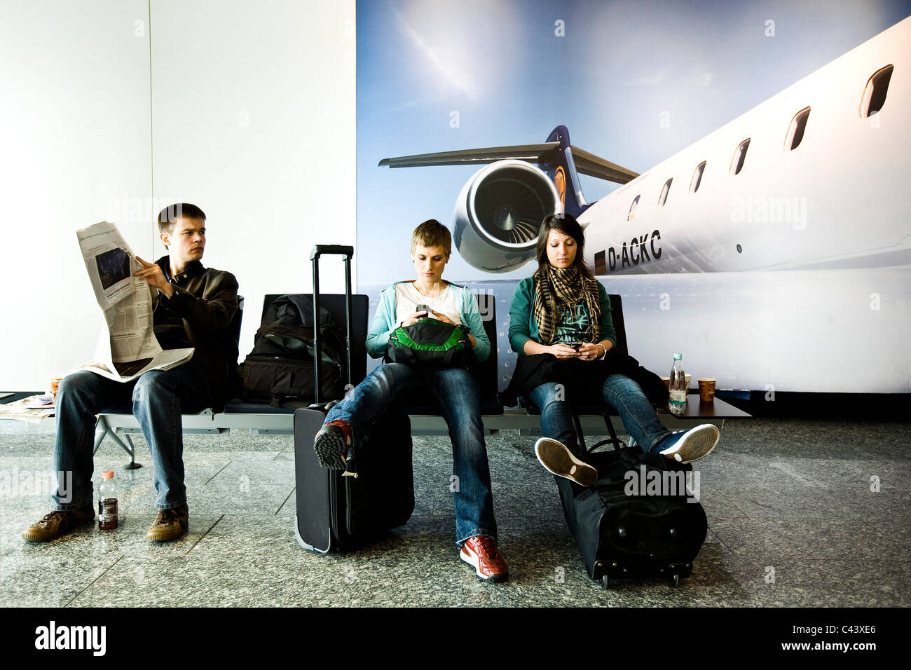 Three young people waiting to depart their flight in Frankfurt airport. - Stock Image