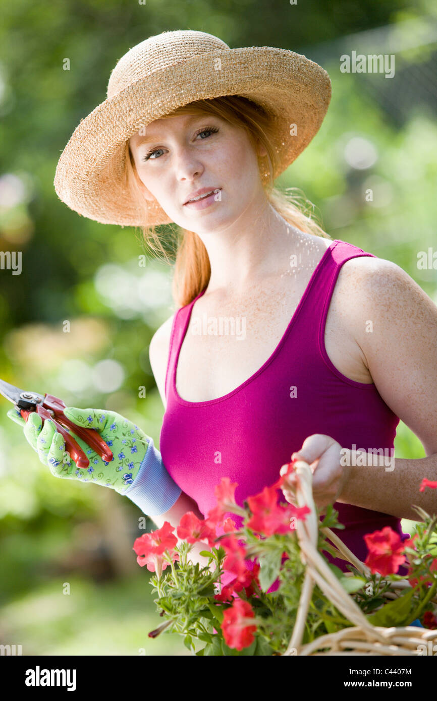 Pretty young woman cutting flowers in her garden - Stock Image