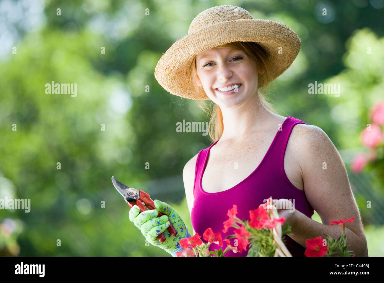 Smiling young woman cutting flowers in her garden - Stock Image