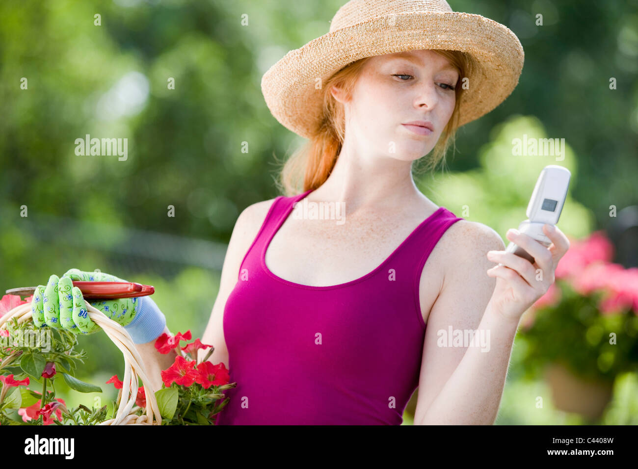 Pretty young woman gardener looking at her cell phone - Stock Image