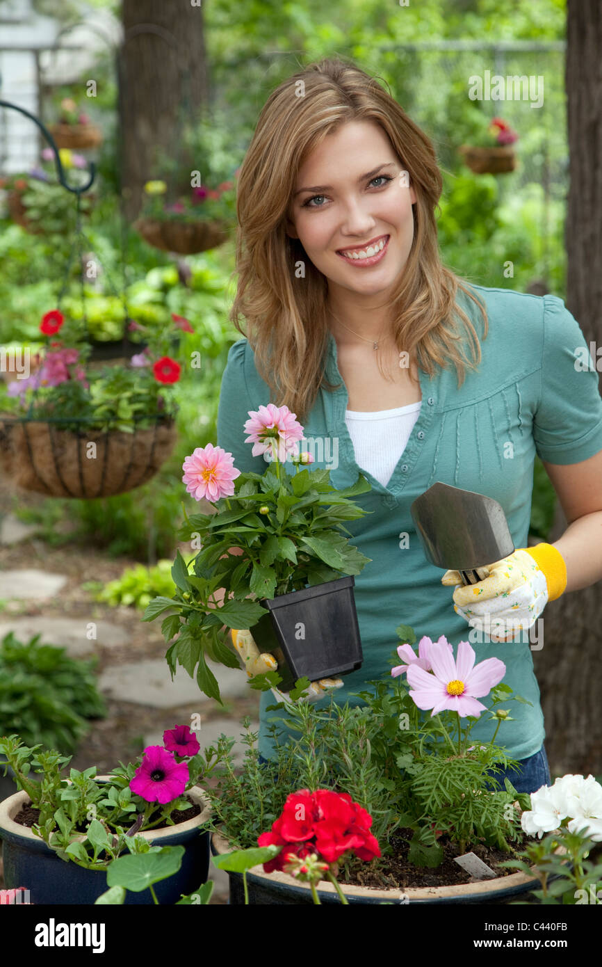Cheerful young woman planting flowers in her garden - Stock Image