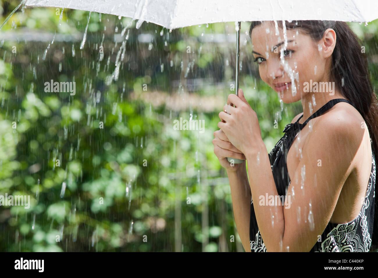 Beautiful Hispanic woman holding umbrella out in the rain - Stock Image