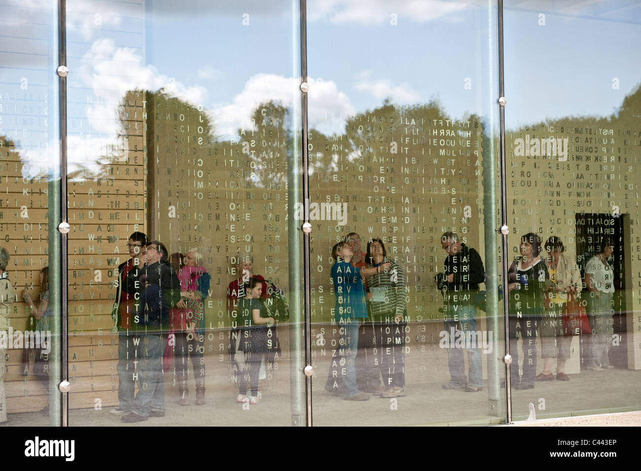 People interacting with Jaume Plensa's a 50-metre curtain of poetry made of suspended steel letters Yorkshire Sculpture Stock Photo