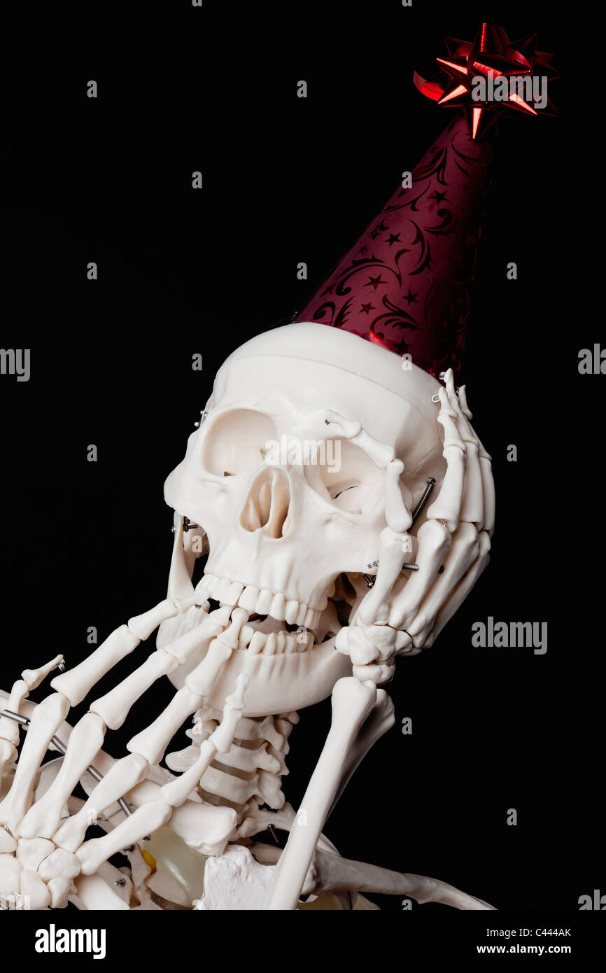 a-skeleton-wearing-a-party-hat-and-looking-surprised-C444AK.jpg