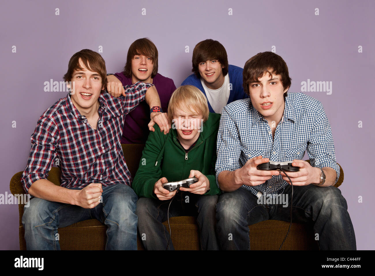 Two teenage boys playing a video game while their friends cheer them on - Stock Image