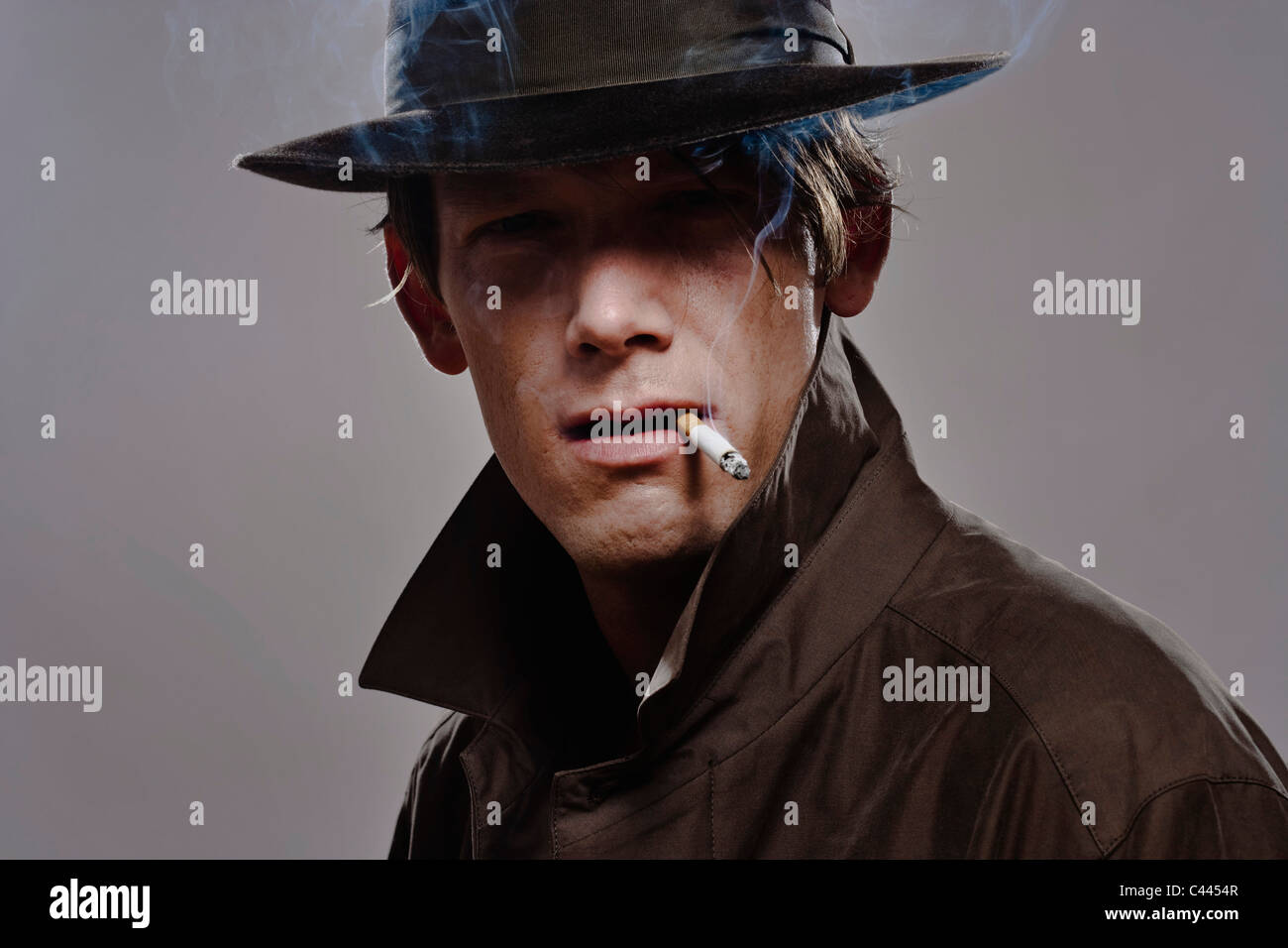 Portrait of a man wearing a hat and trench coat while smoking - Stock Image