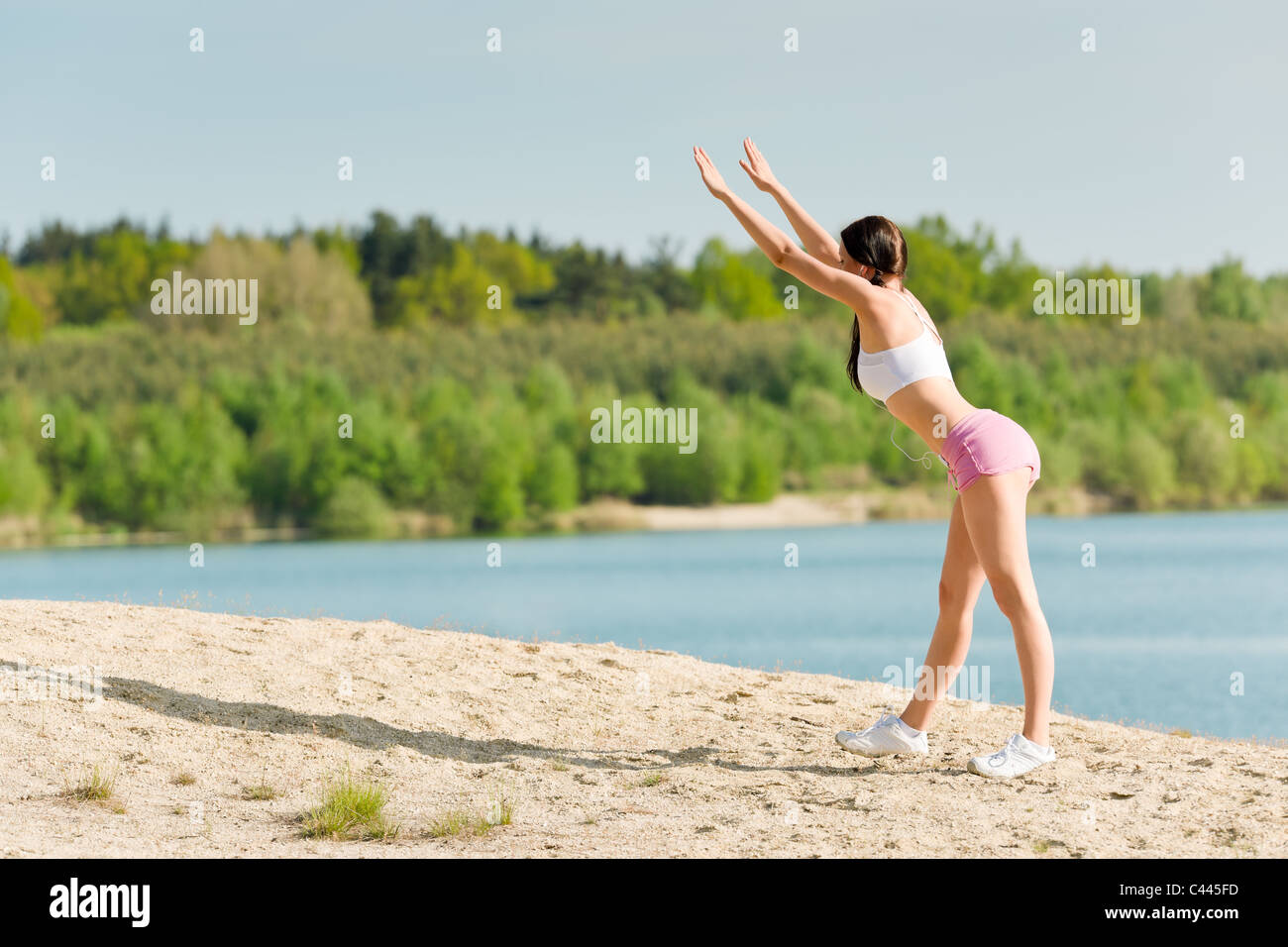 Summer active woman stretching on beach in fitness outfit Stock Photo