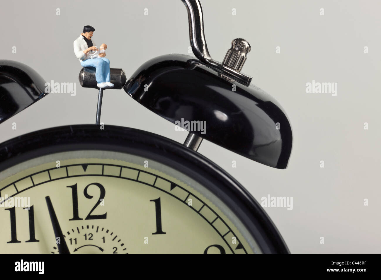 A miniature father figurine holding his baby while sitting on an alarm clock - Stock Image
