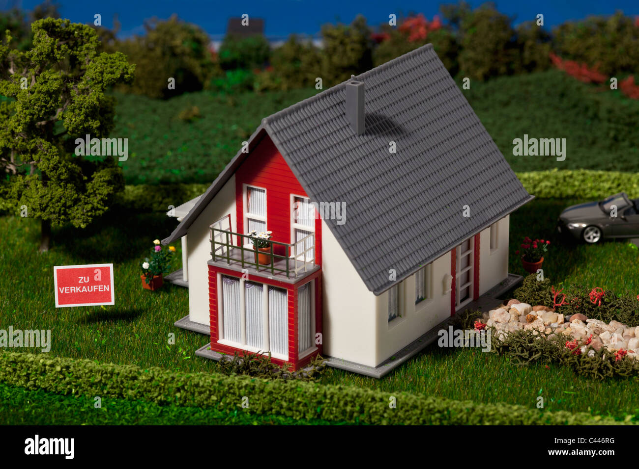 A diorama of a miniature house with a  ZU VERKAUFEN (for sale in German) sign - Stock Image