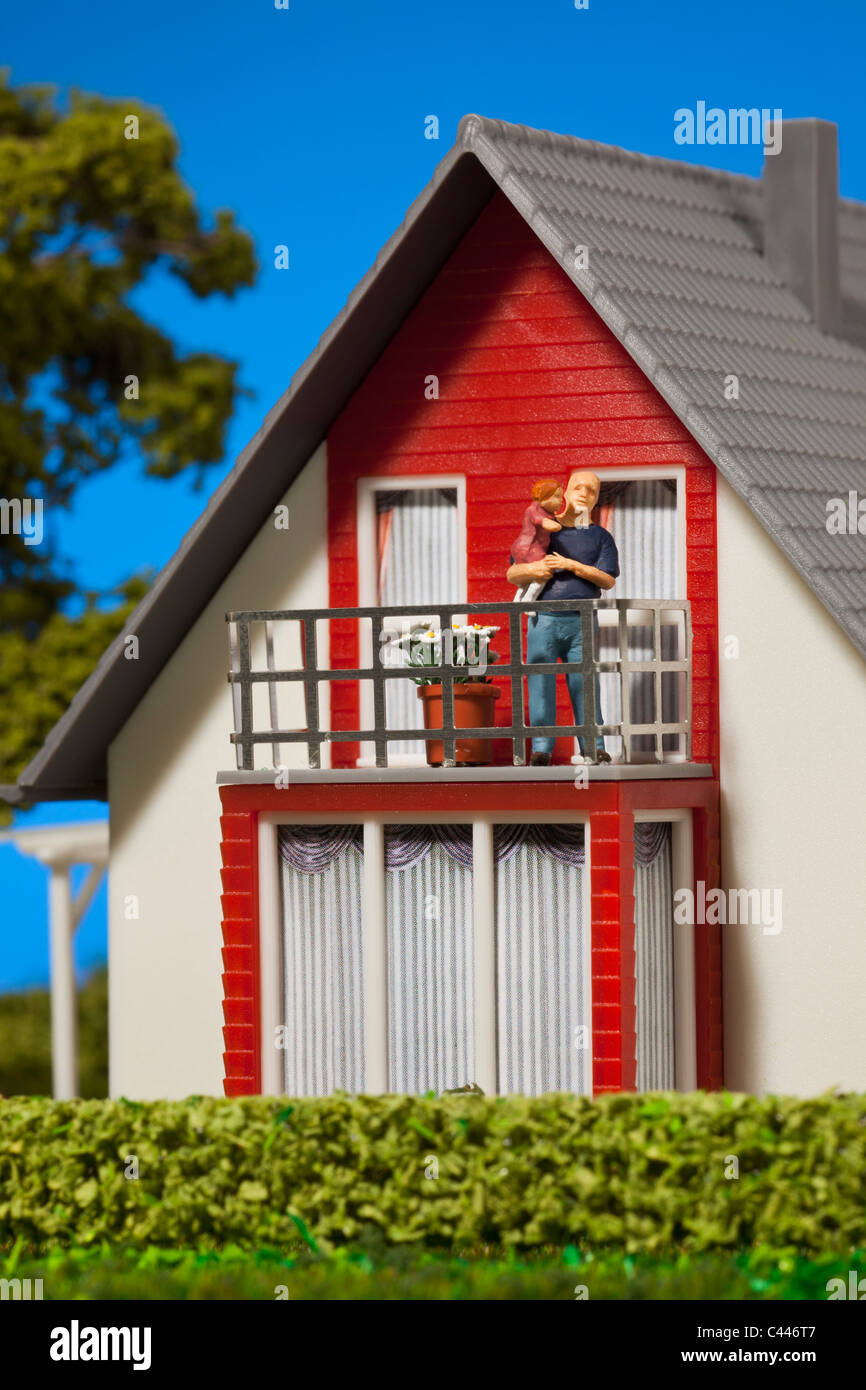 A miniature father figurine holding his daughter on the balcony of a dollhouse - Stock Image