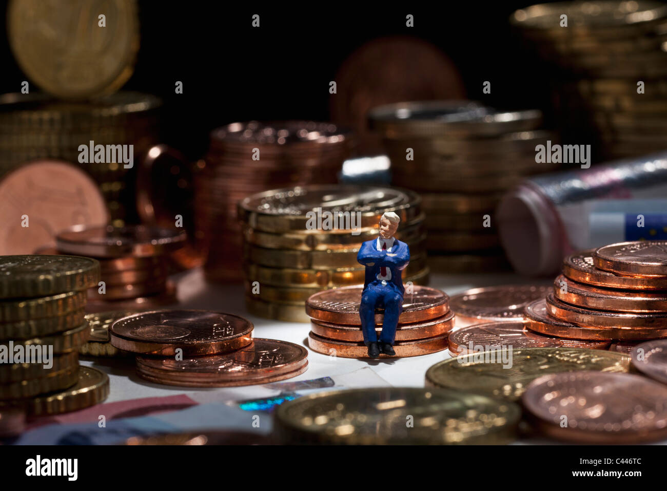 A miniature businessman figurine with arms crossed sitting on a stack of coins - Stock Image